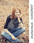 Beautiful red-haired girl in autumn park. Outdoor photo. - stock photo