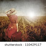 Redhead girl with suitcase at corn field. - stock photo