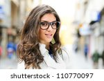 Portrait of a beautiful woman with eye glasses smiling in urban background - stock photo