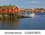 Traditional red rorbu hut with sod roof in town of Reine on Lofoten islands in Norway - stock photo
