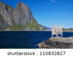Traditional way of drying stock fish on Lofoten islands in Norway - stock photo