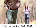 Hiking. Closeup of hiker detail showing hiking poles. Hikers walking in autumn forest. - stock photo