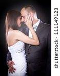 Bride and groom studio portrait over black background - stock photo