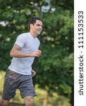 Jogging Healthy Looking Young Man in the Woods Under Morning Sunlight - stock photo