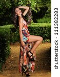 Portrait of a beautiful young woman, model of fashion, in a garden - stock photo