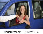 happy woman receiving keys of her new car from dealer - stock photo