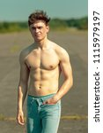 Young adult male standing outside shirtless on a warm summer's day - stock photo