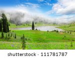 Mountain lake with fog, rock, flowers and trees. Mt. Rainier national Park area. Naches Peak Loop Trail in August. Roundtrip 3.0 miles, Elevation Gain 600 ft Highest Point5849 ft - stock photo
