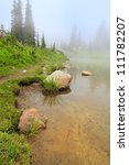 Lake with yellow sand and rocks in the fog: trail with fir trees and wild flowers.  Mt. Rainier national Park. Naches Peak Loop Trail. Roundtrip 3.0 miles, Elevation Gain 600 ft Highest Point5849 ft - stock photo
