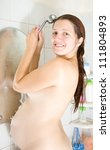 8 months pregnant woman in bath with shower - stock photo