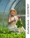 Happy woman picking radish in greenhouse - stock photo