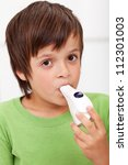 Boy with inhaler breathing - closeup - stock photo