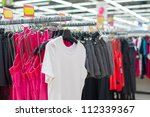 Bright t-shirts and shorts on stands in supermarket - stock photo