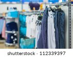 Bright trousers with stripes and t-shirts on stands in supermarket - stock photo