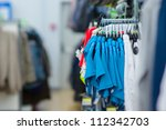 Color T-shirts and sport trousers on stands in supermarket - stock photo