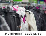 Variety os jackets and vests on stands in supermarket - stock photo