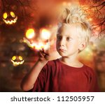 Young Blond Boy Touching Halloween Ghost - stock photo