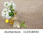 Composition from the bouquet of phloxes and straw angel on a canvas table - stock photo