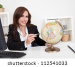 Portrait of a young businesswoman pointing at globe in office - stock photo