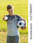 Happy pre-teen boy holding a football in a park - stock photo