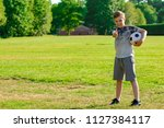 Pre-teen boy holding a football in a park - stock photo