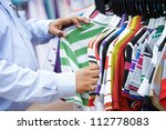 Close-up hands of indian man choosing t-shirt during clothing shopping at store - stock photo