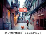 MACAU - AUGUST 1: person with dog walking in narrow street on August 1, 2012 in Macau, China. The Historic Centre of Macao was inscribed on the UNESCO World Heritage List in 2005 - stock photo
