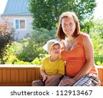 Happy mother and child sits on bench in veranda - stock photo