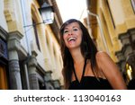 Portrait of an attractive smiling woman in urban background - stock photo