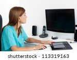 Female dentist using computer at office desk - stock photo