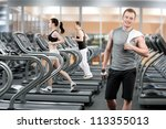 Young man relaxing after running in fitness club - stock photo