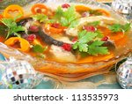 carp in jelly with carrot and cranberry as traditional polish dish on christmas table - stock photo