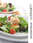 Two plates of scallops, cherry tomatoes and spring mix salad with Saffron dressing. - stock photo