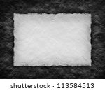 Paper sheet on black rough wall background - stock photo
