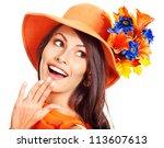 Happy woman wearing orange hat with flower. Autumn fashion - stock photo