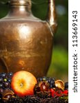 autumnal fruits in front of an antique copper pot - stock photo