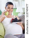 Pregnant woman eating fruits, holding plate with fruits in belly - stock photo