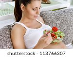 Beautiful healthy pregnant woman  eating vegetable salad - stock photo