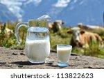 Jug of milk against herd of cows. Switzerland - stock photo