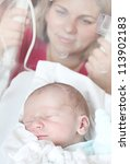 Newborn baby boy sleeping in a incubator. His mother looking at. Close up with shallow DOF. - stock photo