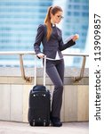 Businesswoman with suitcase using digital tablet and waiting - stock photo