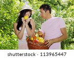 young couple have a fruit basket in the garden - stock photo