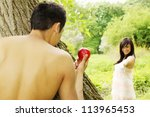 Adam holds out an apple to Eve - stock photo