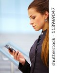 businesswoman using mobile phone outdor over building background - stock photo