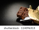 Open bar of chocolate on a black textured background - stock photo