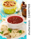 clear red borscht and ravioli (pierogi) filled with sauerkraut and mushrooms for traditional polish christmas - stock photo