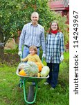 Happy  family with harvested pumpkins in garden - stock photo