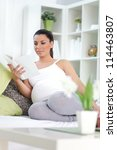 pregnant woman sitting on sofa in living room and reading book. - stock photo