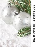 Christmas silver baubles on the snow. - stock photo