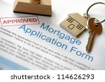 Approved Mortgage loan application with house key and rubber stamp - stock photo